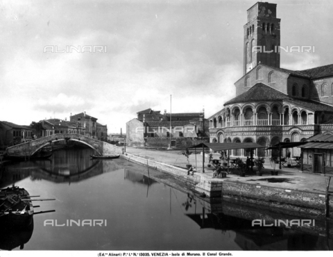 ACA-F-013035-0000 - View of the Grand Canal on the island of Murano in the Venice lagoon. On the right, the side of a church and some people on the banks of the canal are visible. In the background, a bridge and some houses are visible.
