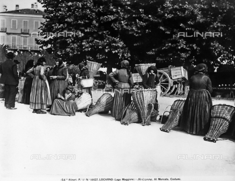 ACA-F-014427-0000 - Women in traditional costume next to wicker chests at a market in Lucerne.