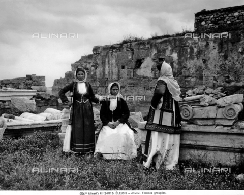 ACA-F-024815-0000 - Portrait of three young women dressed in traditional costume, Eleusi. The ruins of old buildings are visible in the background.