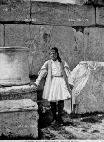 ACA-F-024816-0000 - Portrait of an elderly man dressed in traditional costume, Eleusis. Next him are the remains of some old buildings.