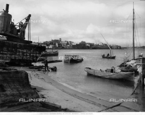 ACA-F-035103-0000 - View of the Port of Brindisi. A man on the beach and some boats are in the foreground. Houses of the city are in the background.