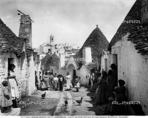 ACA-F-035177-0000 - View of a busy street with cylindrical houses with conical roofs, Alberobello.