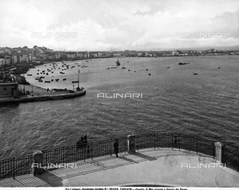 ACA-F-035340-0000 - Panoramic view of porto di Taranto; in the background some industrial establishments are visible, on the left are moored boats and a view of the city, in the foreground, a woman is leaning on the railing of piazzale, observing the view