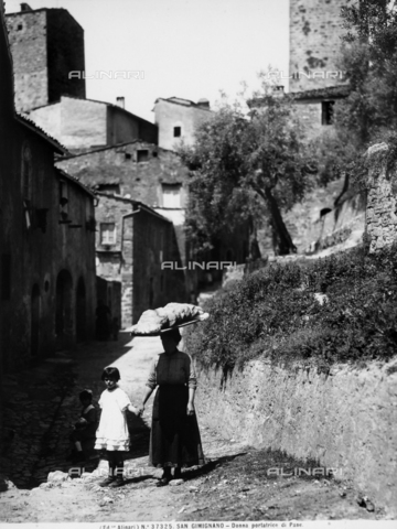 ACA-F-037325-0000 - Ritratto di donna che porta il pane con bambina. Sullo sfondo compare S.Gimignano - Data dello scatto: 1920-1930 ca. - Archivi Alinari, Firenze