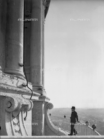 ADA-F-024952-0000 - A visitor leaning on the railing of the balcony of the lantern of the Dome of St. Peter in Rome.
