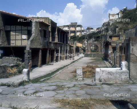 AGC-F-000232-0000 - The decumanus Maximus in Herculaneum. On the left is a large sidewalk and two-story buildings. On the right the columns and remains of buildings. In the background a brick arch - Date of photography: 1989 - Alinari Archives, Florence, Reproduced with the permission of Ministero per i Beni e le Attività Culturali
