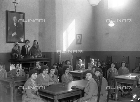 AIL-F-018800-0000 - Young girls in a high school classroom for childcare workers of San Gregorio al Celio in Rome. Under the crucifix a photograph of Benito Mussolini - Data dello scatto: 02/03/1930 - Luce Institute/Alinari Archives Management, Florence
