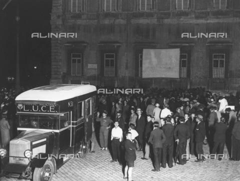 AIL-F-039055-0000 - Folla segue il film proiettato su uno schermo montato sulla facciata del Palazzo Lateranense - Data dello scatto: 25/06/1932 - Istituto Luce/Gestione Archivi Alinari, Firenze