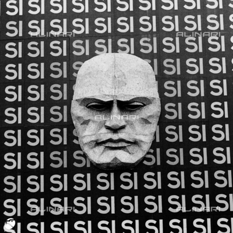 "AIL-F-053504-0000 - Plebiscitary election year XII in Rome: the Palazzo Braschi facade covered by a propaganda poster with the face of Benito Mussolini and the word ""YES"" repeated dozens of times - Data dello scatto: 25/03/1934 - Luce Institute/Alinari Archives Management, Florence"