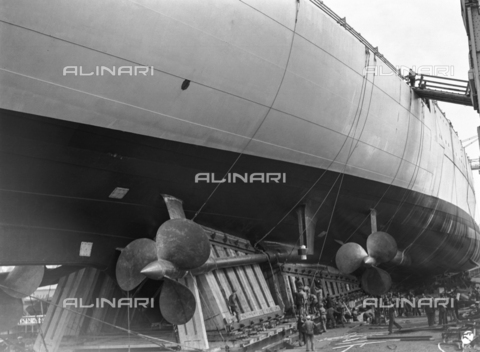 "AIL-F-125610-0000 - Ceremony of the launch of the real ""Roma"" ship in Trieste in 1940: Workers remove support on the side of the ship - Data dello scatto: 09/06/1940 - Luce Institute/Alinari Archives Management, Florence"