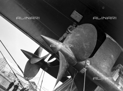 "AIL-F-125611-0000 - Ceremony of the launch of the real ship ""Roma"" in Trieste in 1940: worker on the propeller of the ship - Data dello scatto: 09/06/1940 - Luce Institute/Alinari Archives Management, Florence"