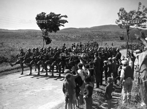 AIL-F-141347-0000 - The Duce's journey to Sardinia: a group of people attend the transition of the Black Diamond Shirts Division. In the background a group of authorities - Data dello scatto: 12/05/1942 - Luce Institute/Alinari Archives Management, Florence