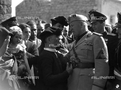 AIL-F-141650-0000 - Duce's journey to Sardinia: Benito Mussolini (1883-1945) with Aldo Vidussoni (secretary of the Fascist National Party) and other authorities entertain with a group of people in traditional Sardinian clothes during his visit to a country along the road between San 'Antioco and Cagliari - Data dello scatto: 15-16/05/1942 - Luce Institute/Alinari Archives Management, Florence