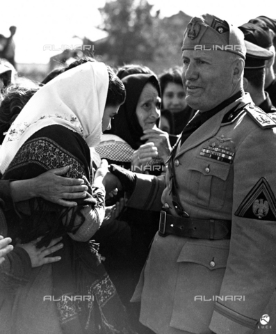 AIL-F-141667-0000 - Duce's journey to Sardinia: Benito Mussolini (1883-1945) with Aldo Vidussoni (secretary of the Fascist National Party) and other authorities shake hands to a woman in traditional Sardinian clothes during her visit to a country along the road between San ' Antioco and Cagliari - Data dello scatto: 15-16/05/1942 - Luce Institute/Alinari Archives Management, Florence