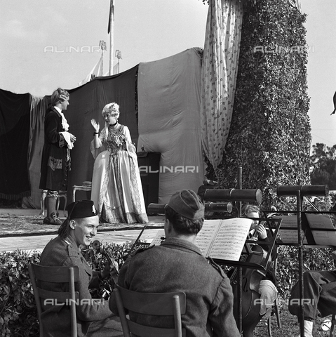 AIL-F-143578-0000 - Boys orchestra of GIL (Italian Youth of the Littorio) and actors during a play set up the camp at the Cascine GIL - Data dello scatto: 03/07/1942 - Luce Institute/Alinari Archives Management, Florence