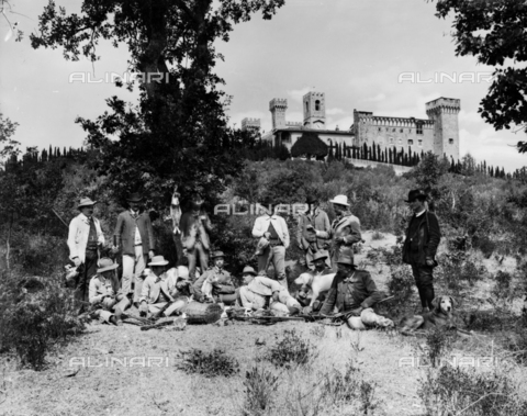 APA-F-000358-0000 - Portrait of a group of hunters in everyday dress, with guns and dogs. Some are drinking wine. In the background, Badia of Passignano