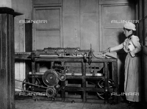 APA-F-005031-0000 - Operaia della Manifattura Tabacchi di San Pancrazio di Firenze accanto ad una macchina - Data dello scatto: 1901 - Archivi Alinari, Firenze
