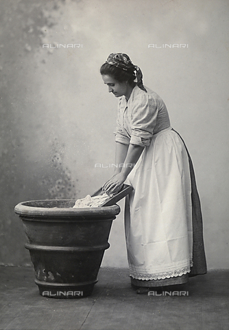 APA-F-005435-0000 - A woman doing laundry in a large terracotta vase