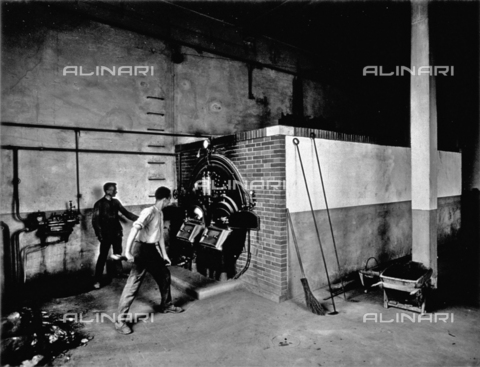 APA-F-008383-0000 - Interior of the Conceria Pedani. Two workers are putting wood into a large furnace