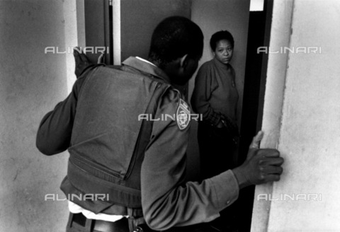 APN-F-014604-0000 - Constable Sibanyoni tries to get access to a flat in Berea  after complaints from the caretaker about drug dealing.1995Photograph: Graeme Williams - South Photographs / Africamediaonline/Archivi Alinari, Firenze