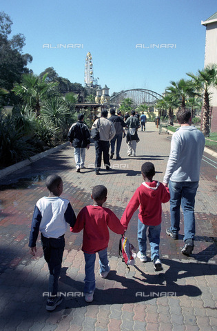 APN-F-014606-0000 - South Africa  Johannesburg  Aug 2003: Sam and John's day out. Aids orphans are taken on a trip to Gold Reef City (Entertainment Park) for a Sunday outing from the Cotlands Home.  Kevin leads three of the children towards the entertainment park  Aids  HIV - South Photographs / Africamediaonline/Archivi Alinari, Firenze