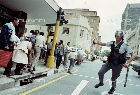 APN-F-014644-0000 - South Africa  Johannesburg  1990: Policeman teargases a crowd after celebrations in Johannesburg streets following the unbanning of the ANC - African National Congress.Photograph: Graeme Williams/ South Photographs - South Photographs / Africamediaonline/Alinari Archives, Florence