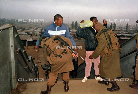 APN-F-014653-0000 - South Africa  Johannesburg  Soweto  1990: Army searches Soweto commuters during the time of ANC - African National Congress and Inkatha Freedom Party. Miltary  passengers  violence  political  unrest.Photograph: Graeme Williams/ South Photographs - South Photographs / Africamediaonline/Alinari Archives, Florence