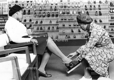 APN-F-036603-0000 - SAED: SOCIAL: 1980 - Fashion. Shoe botique. Ladies fitting shoes (Photograph by Drum Photographer Baileys Archives) pantsula wear - Baileys African History Archive / Africamediaonline/Alinari Archives, Florence
