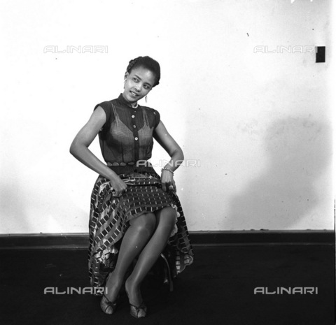 APN-F-116265-0000 - 1956 - Hazel Futa - A Day In The Life Of A Cover Girl - Her temper flared, her beauty glowed, and in a moment I new the Hazel Futa that takes no sass from nobody not even reporters. She 's a woman of spirit, determined to get some place in this dog's life - Africamediaonline/Alinari Archives, Florence, Baileys African History Archive