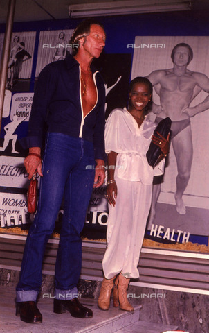 APN-F-116271-0000 - OCT1978 - Bubble Mpondo and Janie Beetge-At the height of their love (and the publicity) Bubbles and Jannie pose in front of a large picture of Jannie. ' The world isn't going to forget us in a hurry'. Muscleman Jannie Beetge told Drum a year ago when his - Africamediaonline/Alinari Archives, Florence, Baileys African History Archive