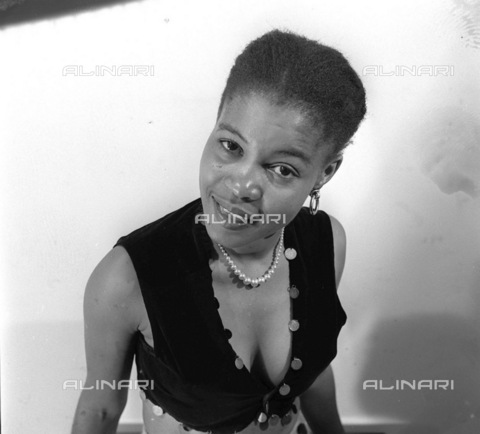 APN-F-116298-0000 - SAED: BEAUTIES: JUN1956 - Cookie Mokapela, Sophiatown's famous socialite, is an advertising model and pin-up. (Photograph by Drum Photographer © Baileys Archives) neg T242, fashion - Africamediaonline/Archivi Alinari, Firenze, Baileys African History Archive