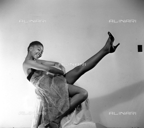 APN-F-116299-0000 - SAED: BEAUTIES: JUN1956 - Cookie Mokapela, Sophiatown's famous socialite, is an advertising model and pin-up. She started a heat wave with this striking pose. (Photograph by Drum Photographer © Baileys Archives) neg T242 model, fashion - Africamediaonline/Archivi Alinari, Firenze, Baileys African History Archive