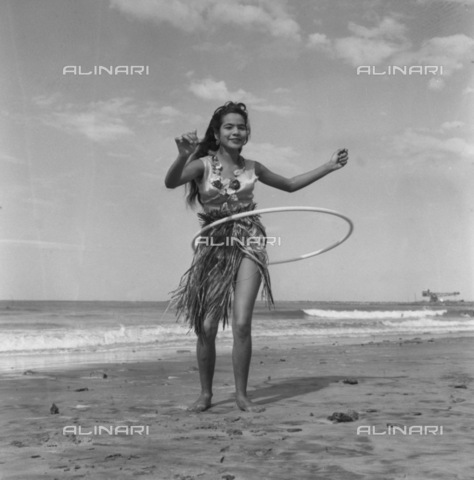 APN-F-116306-0000 - DEC1958 - Muriel Samuels - Hula-Hoop Girl - She's been driven out of the house. Everybody's doing it there. She's been driven off the streets, even the beaches. Most everybody is doing it there. Where else but the open sea for Durban's 16-year-old Muriel - Africamediaonline/Archivi Alinari, Firenze, Baileys African History Archive