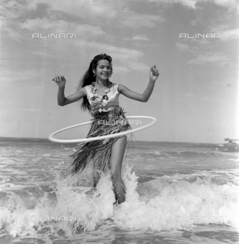 APN-F-116312-0000 - DEC1958 -Muriel Samuels - Hula-Hoop Girl - She's been driven out of the house. Everybody's doing it there. She's been driven off the streets, even the beaches. Most everybody is doing it there. Where else but the open sea for Durban's 16-year-old Muriel S - Africamediaonline/Archivi Alinari, Firenze, Baileys African History Archive