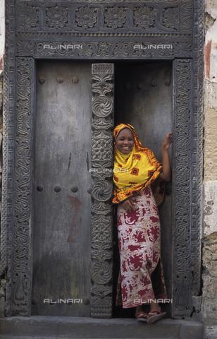 APN-F-132751-0000 - Swahili woman standing in a Zanzibar door, Bagamoyo, Tanzania - Africamediaonline/Archivi Alinari, Firenze