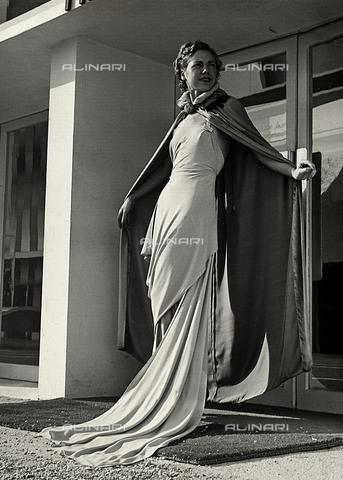"""AVQ-A-000046-0027 - Indossatrice in abito da sera realizzato dalla sartoria """"Graldi"""". Il modello è completato da un mantello in tessuto leggero. - Data dello scatto: 1935 - 1939 - Archivi Alinari, Firenze"""