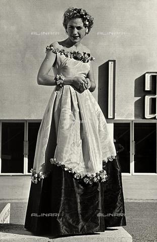 """AVQ-A-000046-0035 - Indossatrice con un abito da ballo realizzato dalla sartoria """"Graldi"""". Il modello è caratterizzato da un'ampia scollatura e una gonna voluminosa con applicazioni di fiori artificiali. - Data dello scatto: 1935 - 1939 - Archivi Alinari, Firenze"""