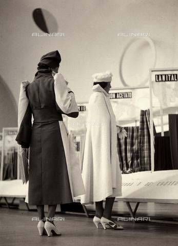 """AVQ-A-000046-0042 - Due indossatrici ritratte da tergo presentano modelli creati dalla sartoria """"Lamma"""". Una modella indossa un soprabito bicolore trattenuto in vita da una fascia. L'altra indossa un'ampia mantella. Cappelli in tinta completano l'insieme. - Data dello scatto: 1935 - 1939 - Archivi Alinari, Firenze"""