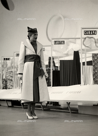 """AVQ-A-000046-0044 - Indossatrice con un soprabito realizzato dalla sartoria """"Lamma"""". Il modello è trattenuto in vita da un'alta fascia e completato da un morbido cappello. L'immagine è stata realizzata in una sala adibita all'esposizione di tessuti. - Data dello scatto: 1935 - 1939 - Archivi Alinari, Firenze"""