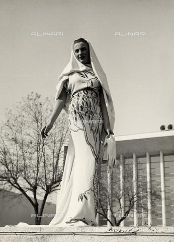 """AVQ-A-000046-0045 - Indossatrice con un abito da sera in tessuto stampato a motivi floreali realizzato dalla sartoria """"Lamma"""". Il modello è completato da un lungo velo. - Data dello scatto: 1935 - 1939 - Archivi Alinari, Firenze"""