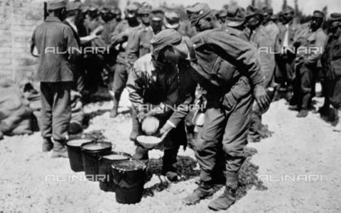 AVQ-A-000057-0061 - L'immagine ritrae un momento della distribuzione del rancio in un campo di prigionia italiano durante la Prima Guerra Mondiale. Si tratta probabilmente del campo di Cuccana in provincia di Udine - Data dello scatto: 1915-1918 - Archivi Alinari, Firenze