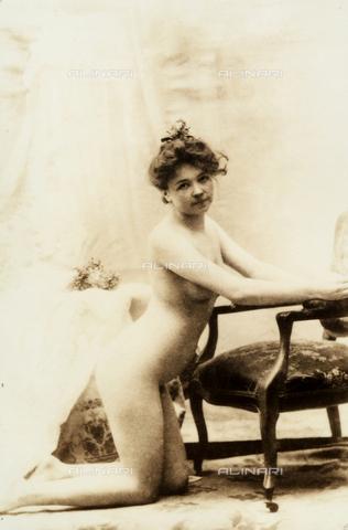 AVQ-A-000065-0232 - Giovane donna nuda ritratta inginocchiata davanti ad una poltroncina. - Data dello scatto: 1910 ca. - Archivi Alinari, Firenze