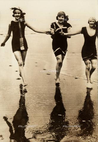 AVQ-A-000065-0377 - Ritratto di tre fanciulle in costume da bagno mentre corrono sulla battigia di una spiaggia. - Data dello scatto: 1920 ca. - Archivi Alinari, Firenze