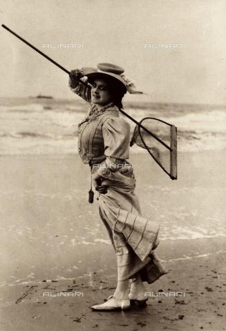 AVQ-A-000065-0382 - Ritratto a figura intera di un'elegante signora sulla battigia di una spiaggia, con un retino da pesca in spalla. - Data dello scatto: 1900 - 1905 ca. - Archivi Alinari, Firenze