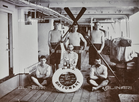 AVQ-A-000204-0070 - Team of oarsmen winners of the 'Chefoo Challenge Cup'. They are dressed in sports clothes and are posing on the main deck of a ship; the name of the team written on a life belt, stands out