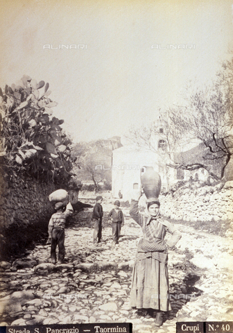 AVQ-A-000209-0018 - The characteristic Via San Pancrazio in Taormina. In the foreground a working class woman is carrying an amphora on her head. At the center of the picture three little boys - Data dello scatto: 1870-1890 ca. - Archivi Alinari, Firenze