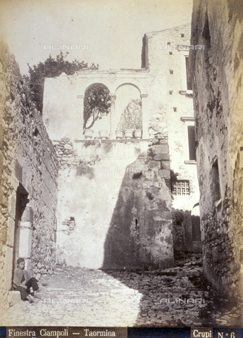 AVQ-A-000209-0027 - A window of Palazzo Ciampoli in Taormina overlooking a characteristic alley of the Sicilian town. On the left a young boy is sitting near a wall - Data dello scatto: 1870-1890 ca. - Archivi Alinari, Firenze