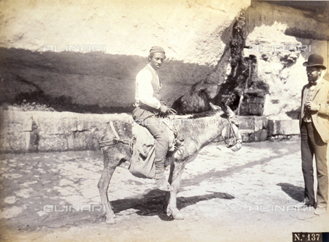 AVQ-A-000209-0033 - Portrait of a young working class man of Taormina on a donkey. A gentleman in late 19th century day dress is observing him - Data dello scatto: 1870-1890 ca. - Archivi Alinari, Firenze