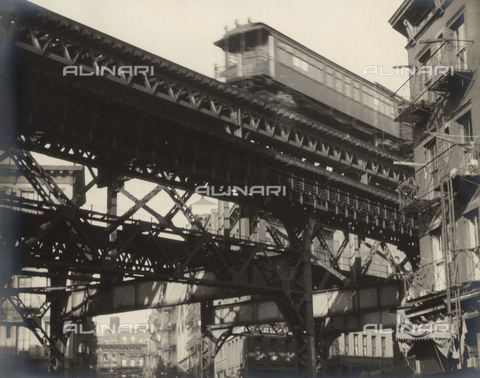 AVQ-A-000756-0008 - A train crossing a railroad bridge between buildings in New York City.