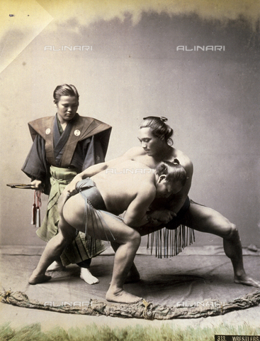 AVQ-A-001344-0105 - Two Japanese sumo wrestlers in a clinch, under the watchful eye of the umpire.